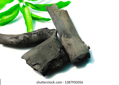 Natural wood charcoal with green leaf on white background