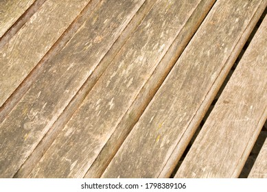 Natural wood flooring outdoors. Diagonal light dirty boards with slots