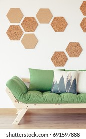 Natural wood, green couch and cork hexagon board tiles in modern organic interior