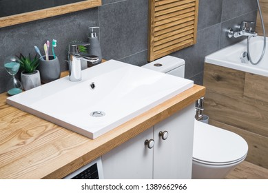 Natural wood table in the bathroom scandinavian style with a white ceramic sink and bathroom accessories.