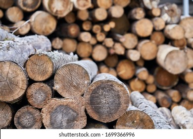 Natural wooden background - closeup of chopped firewood. Firewood stacked and prepared for winter Pile of wood logs.