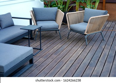 Natural wooden floor terrace with nice sofa and chairs with grey textile materials.