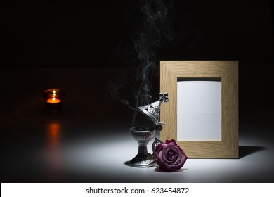 natural wooden picture frame with thurible, pink rose and candle light on dark background