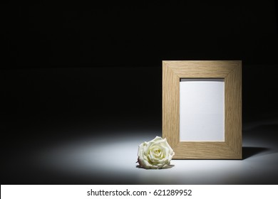 natural wooden picture frame with white rose on dark background