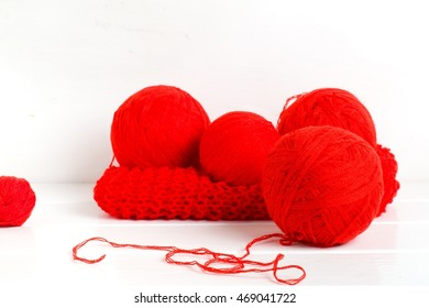 Natural woolen yarn and knitting on white wooden background.selective focus