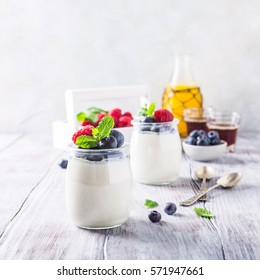 Natural yogurt with berries on light gray background. Copy space. Healthy breakfast concept.