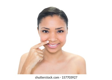 Natural young dark haired model pointing her nostril with her finger on white background