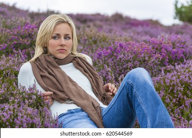 A naturally beautiful sad depressed young blond woman in a field of purple heather flowers