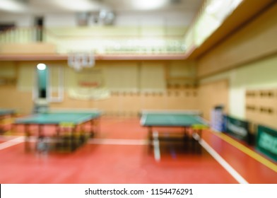 Naturally blurred interior of modern gym with tables for ping-pong