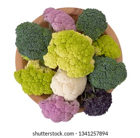 Naturally colourful vegetables on wooden plate, isolated on white. Assorted raw cauliflower, broccoli, purple sprouting florets. Healthy assortment.