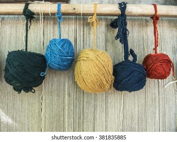 Naturally dyed balls of yarn in white, red, blue, yellow and green