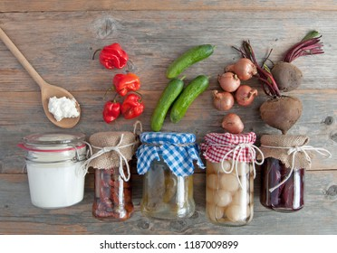 Naturally fermented foods in jars including kefir, gherkins and peppers and onions