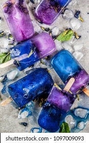 Naturally organic summer sweets, homemade blue and violet ice cream popsicles with butterfly pea flower tea, grey concrete background copy space
