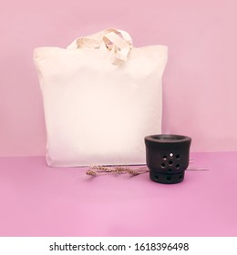 Nature and aromatherapy concept of an organic cotton bag mock up, black porcelain aromatherapy oil diffuser and natural dried wheats on pink background