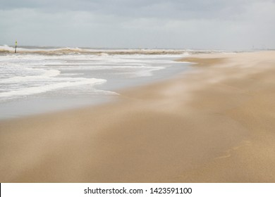 Nature background featuring sand gone with wind in summer windy day on North Sea coast near the Hague in the Netherlands. Abstract sand surface illustrating stormy weather and blowing wind.