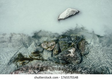 Nature background with mossy stones on silver water of mountain river. Silver sand on sandy bottom of mountain river. Shine on milky river surface. Gray nature backdrop with clear water with sand.