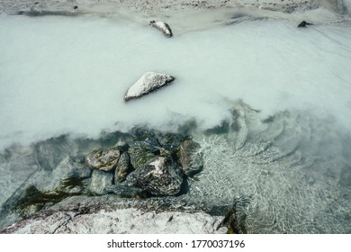Nature background with mossy stones on silver water of mountain river. Silver sand on sandy bottom and shore of mountain river. Milky river surface. Gray nature backdrop with clear water with sand.