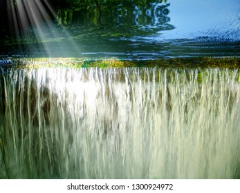 Nature background: romantic waterfall, transparent waters illuminated by sunrays