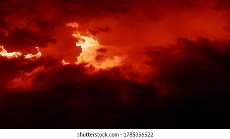 Nature background with stormy clouds. Dark dramatic sky with a stormy clouds before the rain. Image in dramatic dark red tone