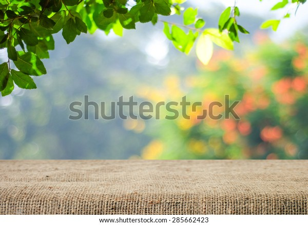 Nature background and table wood for product display template, Empty wooden table and  sack tablecloth over blur green tree at park, garden outdoor with bokeh light background
