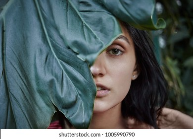 Nature, beauty, skincare and organic cosmetics concept. Half face close up portrait of gorgeous bob haired young woman with clean skin posing outdoors, hiding herself behind large fresh green leaf