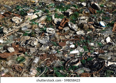 Nature contaminated by glass metal plastic wasteDiscarded household garbage on the meadowEnvironmental pollution and ecology problem concept.Human health hazard concept.