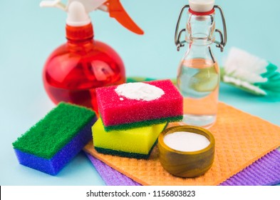 Nature and eco friendly homemade natural cleaners baking soda, white vinegar in vintage bottle, washing sponges for cleaning home, non toxic cleaning products, isolated on blue background.