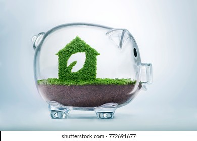 Nature is home concept. Grass growing in the shape of a house with a cut out leaf, inside a transparent piggy bank, symbolising the need to invest in sustainable homes, to protect the environment.