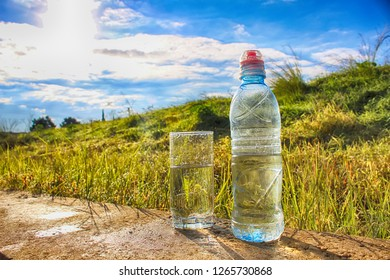 Nature in Israel. Cold mineral water in a glass and in a bottle against the background of a beautiful field and blue sky. Raindrops and Dew Drops on the grass