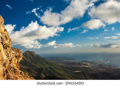 Nature and landscape of the Canary Islands - Mountains and nature of Gran Canaria. Green mountains, coastal villages, small pine trees and cloudy sky above ocean. Gran Canaria, Canary Islands, Spain