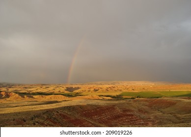 nature landscape of fields and heavy clouds with rainbow in mountains, wyoming, usa
