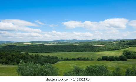 Nature landscape, green hills in summer with blue sky, Siena, Italy.