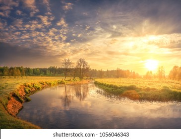 Nature landscape of spring river on morning dawn. Bright sun lights on green grass and young foliage. Rural scene. Trees on shore of river and colorful sky with clouds shining on warm sunlight