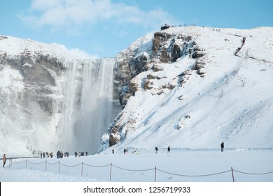 Nature Landscape view of Beautiful Skogafoss Waterfall, cliffs of former coastline. Famous popular tourist attraction Visitors travel in Winter highland of Europe, Landmark scene destination Iceland.