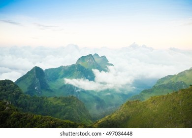Nature landscape view of green peak mountains and blue sky with clouds fog flow