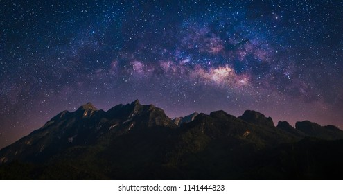 Nature landscape view of mountain range with universe space of milky way galaxy and stars on night sky