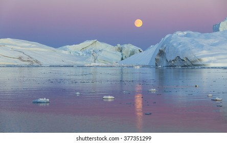 Nature and landscapes of Greenland. Travel on the scientific vessel among ices. Studying of a phenomenon of global warming. Ices and icebergs of unusual forms and colors. Midnight