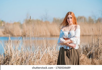 Nature look, Medieval style of clothes, redhead woman in cotton vintage blouse, belt and skirt