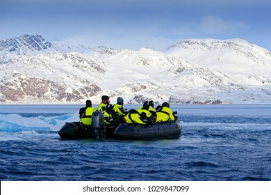 Nature lovers in Arctic Svalbard, Norway. Motor boat with tourists on the ice sea, snowy mountain in background. Arctic cruise in winter, black powerboat with photographers.