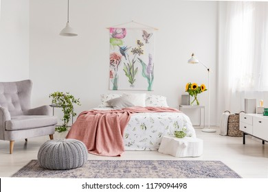 Nature lover's bright bedroom interior with a wall art of flowers and birds painted on a fabric above a bed which is dressed in green plants pattern on white linen. Real photo.
