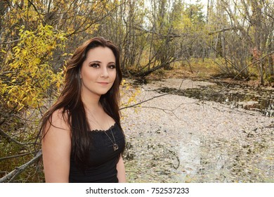 Nature loving girl with long dark hair standing by a pond in a black tank top with yellow leaves in the background