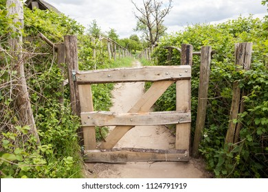 in the nature near the fruit trees there is this wooden fence for the protection of farming animals