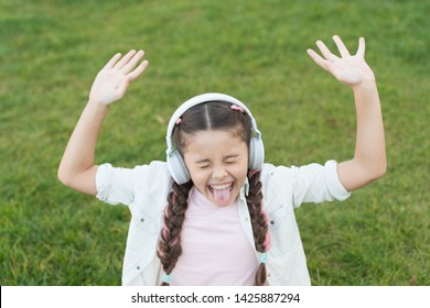 Nature is the one song of praise that never stops singing. Happy song singer on green grass. Little girl singing song playing in headphones. Cute small child doing vocal on song on summer outdoor.
