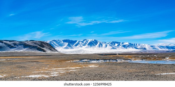 Nature panoramic landscape at the new road construction site in Mongolia with the snow mountain against the blue sky and the stream of snow melting water in summer season