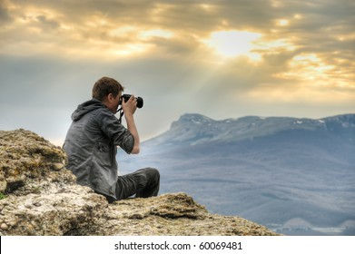 Nature photographer with digital camera on top of the mountain. HDR.