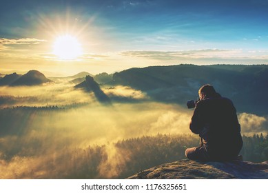 Nature photographer on a mountain cliff taking picture of landscape awaking in mist. Tourist with camera and tripod in cold weather