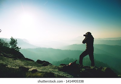 Nature photographer stay at tripod on summit and thinking. Man photographer during hike. Photographer taking photos outdoor by dslr camera.