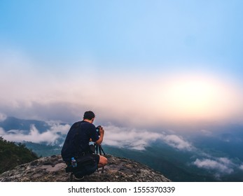 Nature photographer takes photos with camera on tripod at cliff. Dreamy foggy landscape. Morning sunrise  blue misty in beautiful valley below.