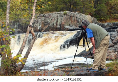 Nature Photographer taking a photo of a Waterfall with Autumn colors in the background