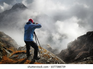 Nature photographer tourist with camera shoots while standing on top of mountain in Himalaya mountains.Beautiful inspirational landscape, trekking and activity.